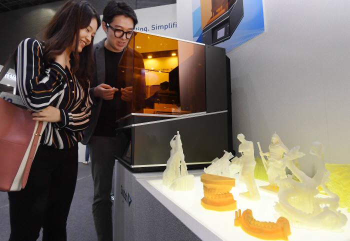 27일 경기 고양시 킨텍스에서 열린 '인사이드 3D프린팅'에서 관람객이 신도리코의 SLA프린터를 살펴보고 있다. 이동근기자 foto@etnews.com