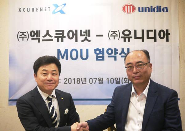 김용건 엑스큐어넷 대표(오른쪽)와 이성중 유니디아 대표가 조달총판 업무협약 체결 후 악수하고 있다.
