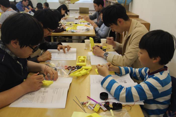 한화시스템이 지역 어린이를 위해 마련한 주니어과학교실에 참가한 어린이들이 모형을 만들고 있다.