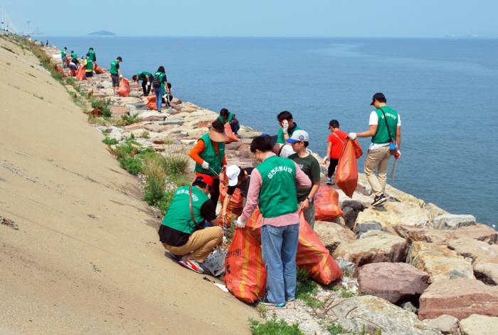 삼천리 임직원들이 시화방조제 환경 정화 봉사활동을 벌이고 있다.