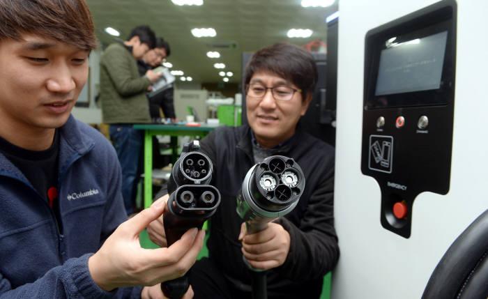 국내 전기자동차 급속 충전기 표준 방식은 콤보(TYPE1)로 통일됐다. 시그넷시스템 직원이 콤보1(왼쪽)과 일본 차데모 커넥터를 비교하는 모습. <전자신문DB>