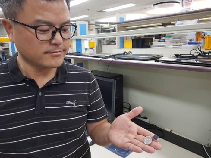 이주현 ETRI 박사가 시각지능 칩 크기를 동전과 비교하는 모습.