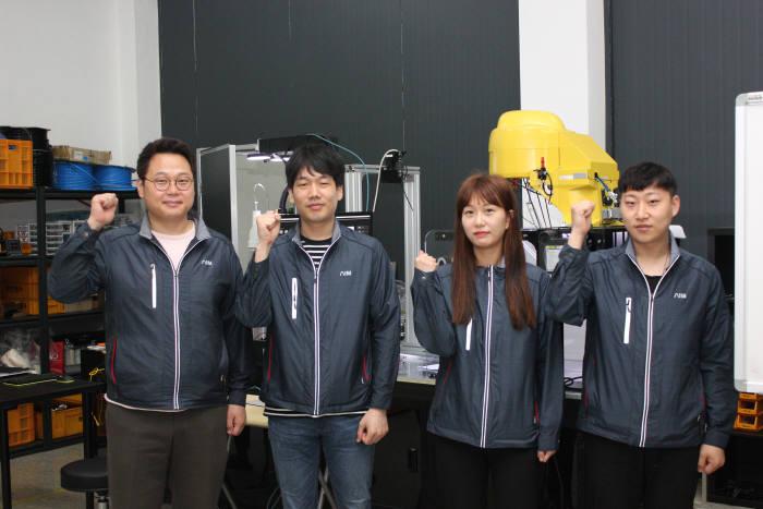심훈 에이아이엠 대표(왼쪽)와 직원이 스마트팩토리 장비 앞에서 화이팅을 외치고 있다.