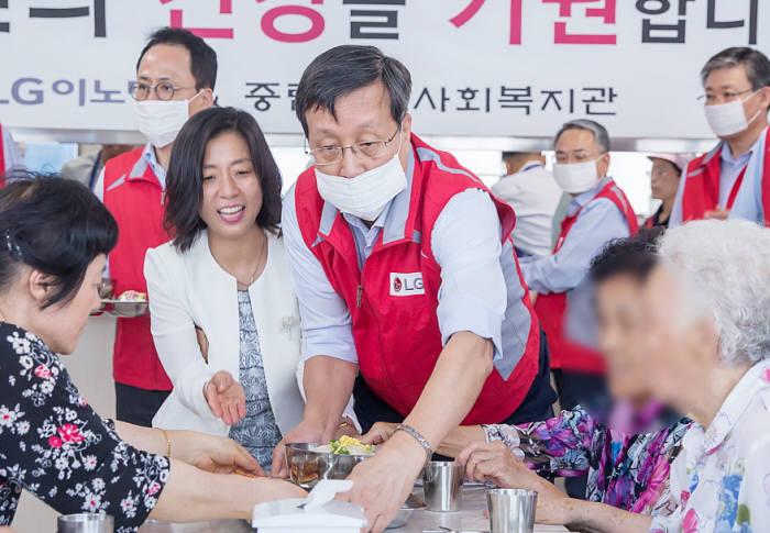 박종석 LG이노텍 사장(가운데)이 위생마스크를 쓰고 삼계탕을 나눠 드리고 있다.