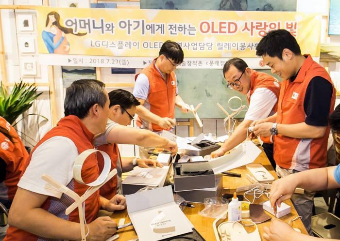 LG디스플레이 OLED조명사업담당 박성수 상무(오른쪽 두번째)를 비롯한 임직원이 미혼모를 위한 OLED수유등을 직접 제작하고있다. (사진=LG디스플레이)