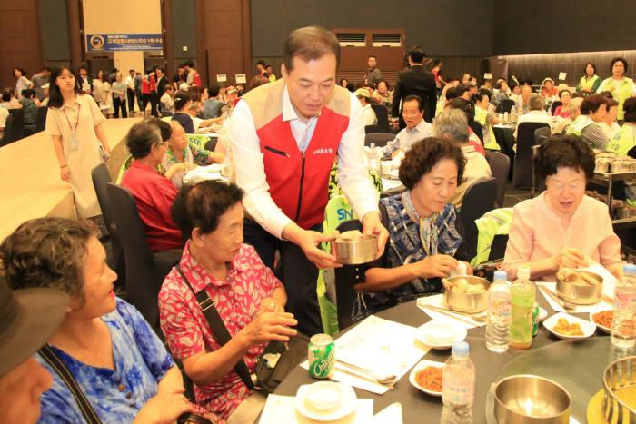 이완신 롯데홈쇼핑 대표(가운데)가 어르신들에게 삼계탕을 대접했다.