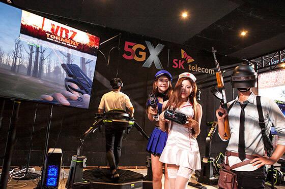 SK텔레콤은 지난 9일 5GX 게임 페스티벌 개최 소식을 전하며 옥수수 소셜 VR 서비스를 연내 상용화할 계획을 밝혔다. 사진은 10일 10일 오전 일산 킨텍스에서 열린 5GX 게임 페스티벌에서 실감형 VR 게임을 즐기는 관람객을 배경으로 인기게임 리그오브레전드(LoL), 배틀그라운드 캐릭터의 코스프레를 선보이고 있는 장면 [