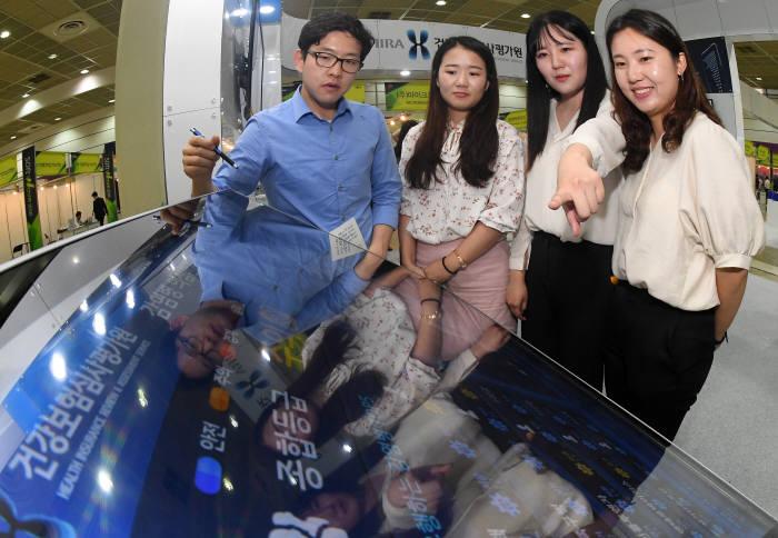 8~10일 서울 삼성동 코엑스에서 열린 소프트웨이브 2018 행사에서 관람객이 건강보험심사평가원 부스에서 감염병 의심환자 조기 감시시스템을 살펴보고 있다. 이동근기자 foto@