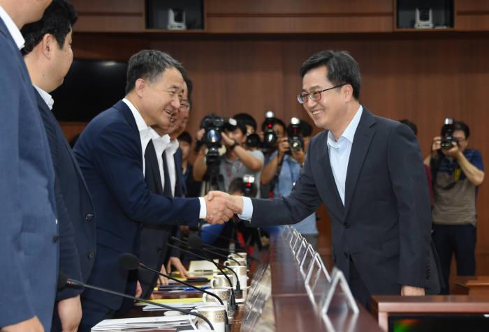 김동연 경제부총리 겸 기획재정부 장관(오른쪽)이 혁신성장 관계장관회의에서 박능후 보건복지부 장관과 악수하고 있다.