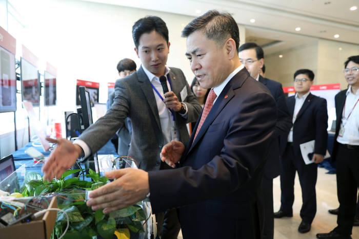 롯데정보통신 본사에서 열린 프로젝트 전시회에서 신입사원이 마용득 대표에게 아이디어를 설명하고 있다.
