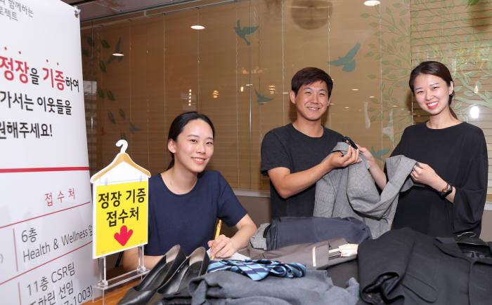 LG디스플레이 임직원 100여명이 정장 의류와 소품 600여점을 열린옷장에 기부했다. 임직원들이 정장을 기부하고 있는 모습. (사진=LG디스플레이)