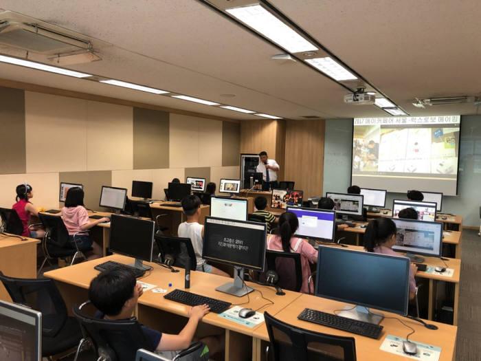최만 유안초 교사가 지난주 토요일 롯데정보통신에서 열린 제5회 드림업 SW교육에서 학생에게 프로그램을 설명하고 있다.