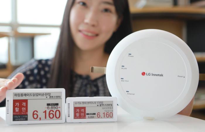 LG이노텍 직원이 리모콘 통합형 ESL(사진 왼쪽)과 IoT무선중계기(오른쪽) 등 최신 유통 IoT 솔루션을 선보이고 있다. (사진=LG이노텍)