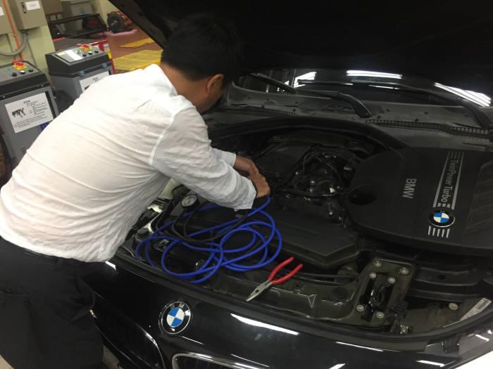 최영석 선문대 교수가 BMW GT 차량에 바이패스 밸드 개폐 여부를 확인할 수 있는 진공측정기를 장착하고 있다.