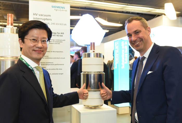 허정석 일진전기 부회장(왼쪽)과 세드릭 나이케 지멘스 부회장이 프랑스 파리에서 열린 2018 국제 대전력망 기술협의회에서 친환경 가스절연개폐장치의 핵심부품을 선보이고 있다. (사진=일진전기)