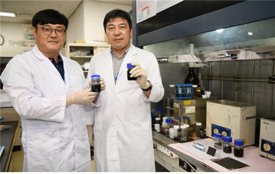 이건웅 KERI 책임연구원(오른쪽)과 정승열 책임연구원이 새로 개발한 그래핀-실리콘 복합 음극재를 들고 포즈를 취했다.