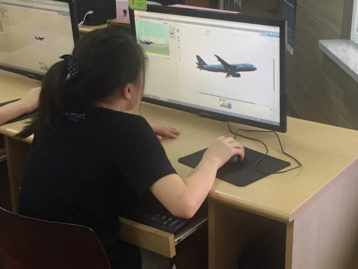 먼우금초 학생이 비행기 모양을 조정하고 있다.