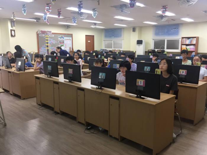 먼우금초 학생이 컴퓨터교실에서 수업을 듣고 있다.