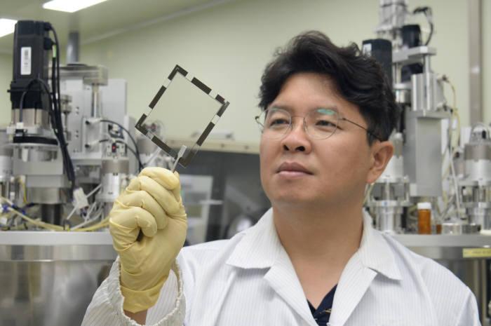 조남성 ETRI 유연소자연구그룹장이 유기 나노렌즈 제작 샘플을 점검하는 모습.