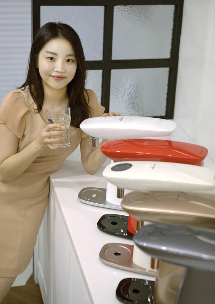 웅진렌탈 모델이 무약정 정수기 신제품 조약돌 정수기 미니를 소개하고 있다.
