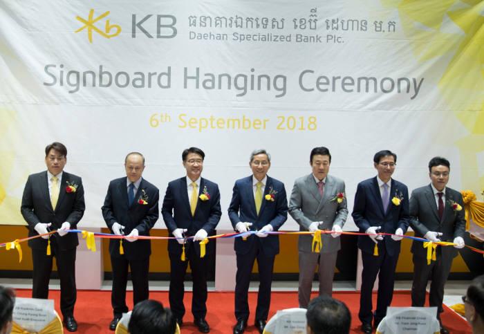 KB금융 계열사인 KB국민카드는 6일 캄보디아 프놈펜에서 첫 해외 자회사인 KB 대한 특수은행을 열었다. 윤종규 KB금융그룹 회장(왼쪽 네 번째), 이동철 KB국민카드 사장(왼쪽 세 번째), 오세영 LVMC홀딩스 회장(왼쪽 다섯 번째) 등 개소식 참석자들이 기념 테이프를 자르고 있다.