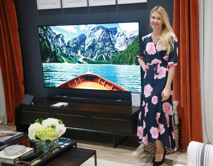 LG전자가 CEDIA 2018에서 유명 인테리어 디자이너와 협업해 LG 올레드 TV AI 씽큐와 조화되는 우아한 거실을 연출했다. LG전자 부스를 디자인한 케이트럼슨이 LG 올레드 TV AI 씽큐 옆에서 포즈를 취하고 있다.