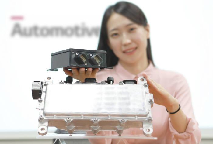 LG이노텍 직원이 전기차 부품인 DC-DC(직류-직류)컨버터와 전기차 충전용 통신 컨트롤러(EVCC)를 선보이고 있다. LG이노텍은 이 제품들을 뛰어난 품질로 공급해 GM으로부터 품질 우수상을 받았다.(사진=LG이노텍)