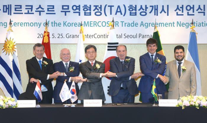 지난 5월 25일 서울에서 열린 한-메르코수르 무역협정(TA) 협상개시 선언식에서 김현종 통상교섭본부장(왼쪽서 세번째)과 각국 대표들이 손을 맞잡고 있다.