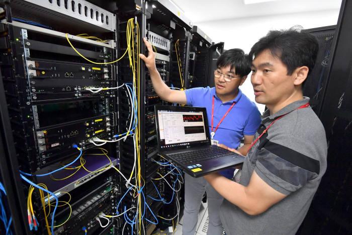 SK텔레콤 퀀텀테크랩 연구원이 양자암호통신 장비를 점검하고 있다.