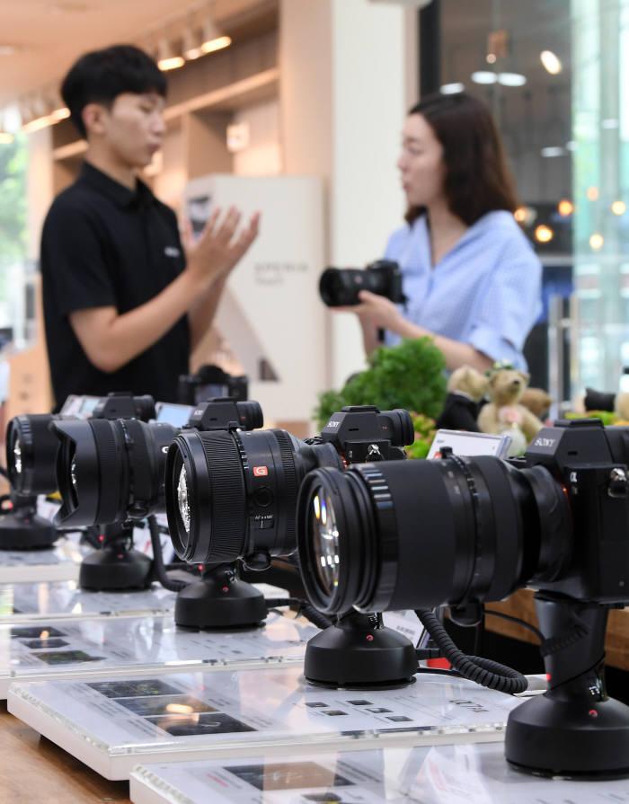 서울 강남구 소니스토어에서 소비자가 카메라와 렌즈를 살펴보고 있다.<전자신문 DB>