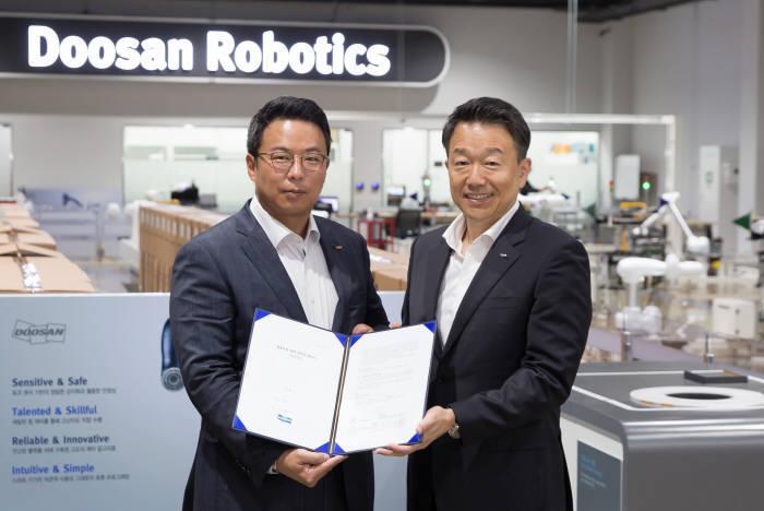 신동진 인아엠씨티 대표(왼쪽)와 이병서 두산로보틱스 대표가 대리점 계약서를 들고 기념촬영했다.
