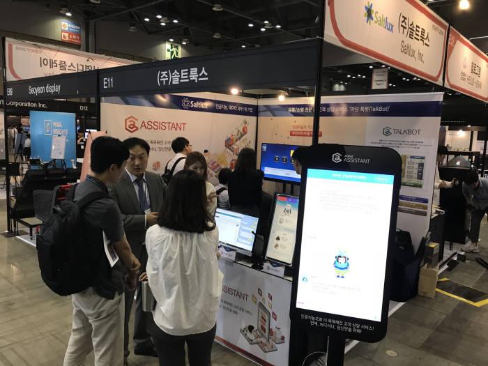지난달 열린 2018 K SHOP 2018 행사에서 솔트룩스 관계자가 부스를 방문한 유통·쇼핑업계 관계자에게 인공지능(AI) 톡봇을 소개하고 있다. 솔트룩스 제공
