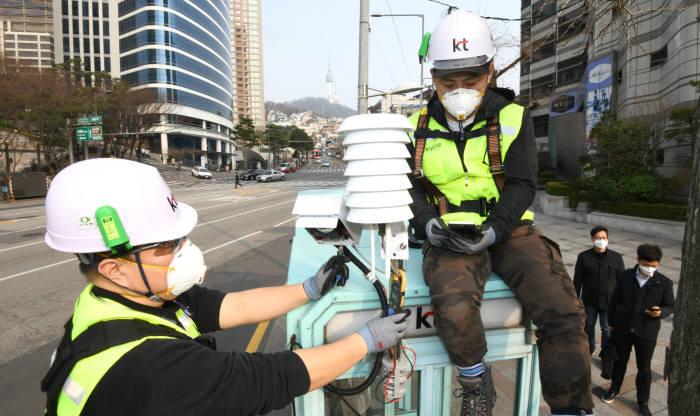 서울 용산구 공중전화 부스에서 KT 직원이 공기 질 측정기를 설치하는 모습.