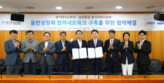경기테크노파크 및 삼성증권 관계자가 11일 경기도 안산 경기테크노파크에서 협약서를 교환하고 있다.