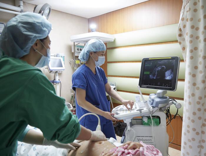 강남차병원 의료진이 역아 산모에게 초음파를 보며 역아외회전술을 실시하고 있다.