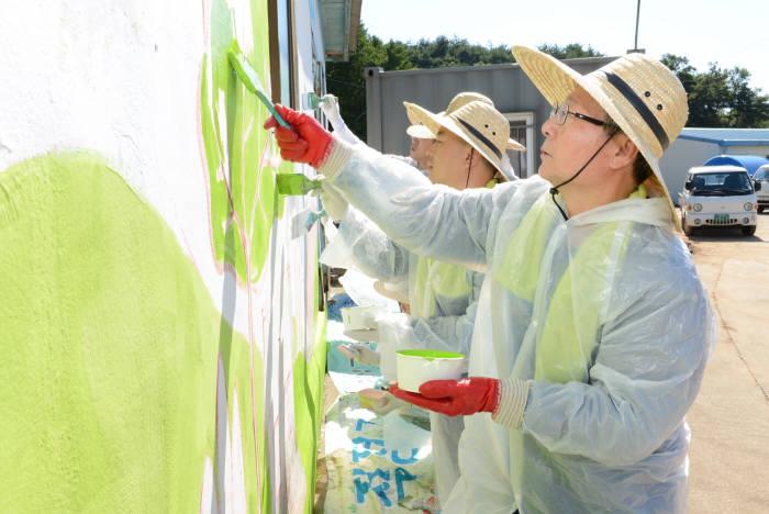 오병관 NH농협손해보험 대표가 헤아림 봉사단원들과 벽화를 그리고 있다.