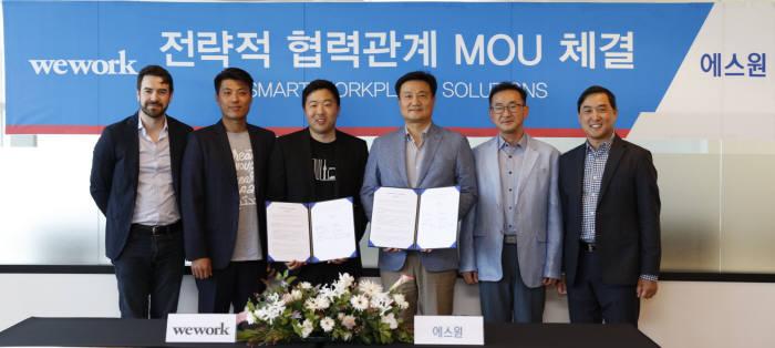 에스원은 13일 위워크와 스마트 워크플레이스 솔루션 업무협약을 체결했다. 매튜 샴파인 위워크 코리아 대표(왼쪽 세번째)와 권영기 에스원 전무(왼쪽 네 번째)가 협약서를 들어보이고있다.