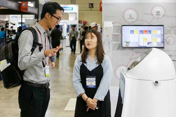 13일 서울 삼성동 코엑스에서 열린 2018 사물인터넷 국제전시회에서 LG CNS 직원이 참관객에게 로봇 서비스 플랫폼 오롯을 소개하고 있다. LG CNS 제공