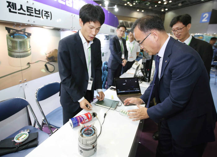 이상홍 한국에너지공단 이사장 직무대행(앞줄 오른쪽)이 4일 2018 대한민국 에너지대전 국민참여관(에너지1번가)에서 젠스토브가 선보인 전기를 생산하는 캠핑용 가스 스토브를 체험하고 있다.
