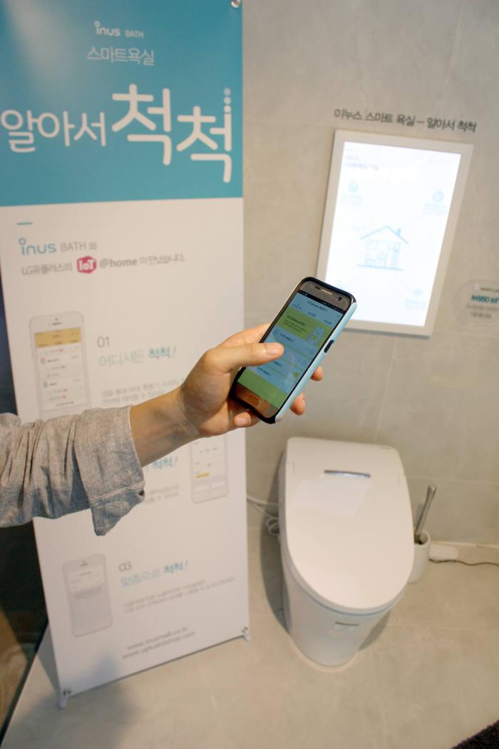 이누스바스 관계자가 이누스바스의 IoT 탑재 비데일체형 양변기를 스마트폰으로 원격 제어하는 모습.