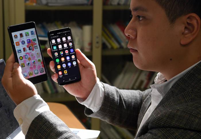 북한에서 사용하는 스마트폰 평양 터치(모델명 평양 2418)를 본지에서 입수했다. 본지 취재진이 같은 안드로이드 기반의 평양 터치와 국내 스마트폰을 비교해 보고 있다. 이동근기자 foto@etnews.com