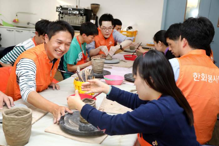 한화케미칼 임직원들이 서울 서대문장애인복지관에서 장애인들과 도예체험을 하고 있다.
