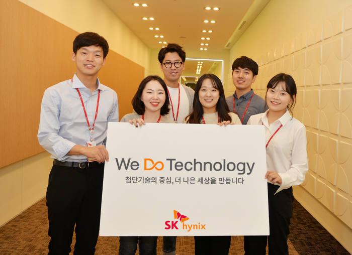 SK하이닉스 직원들이 새 슬로건 We Do Technology가 새겨진 팻말을 들고 있다.<사진 SK하이닉스>