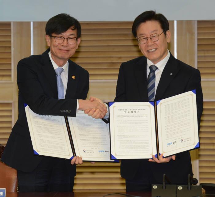 김상조 공정거래위원장(왼쪽)이 이재명 경기도지사와 협약서를 들고 기념촬영을 했다.