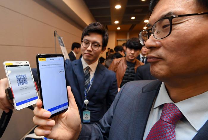 한국조폐공사는 2018년 위·변조방지 보안기술 설명회를 25일 서울 중구 대한상공회의소에서 개최했다. 조용만 한국조폐공사 사장이 블록체인 기술을 활용한 KOMSCO 신뢰플랫폼 기반 QR코드 결제 시연을 하고 있다.