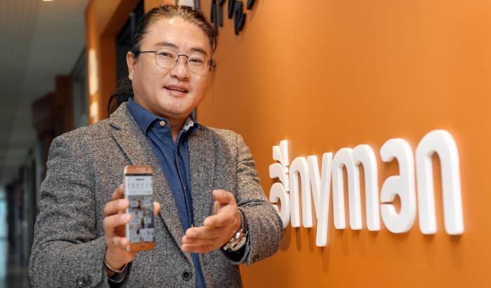윤주열 에이에스엔 대표이사가 누구나 참여할 수 있는 재능·시간 공유 애플리케이션 애니맨을 스마트폰 위에 직접 띄워보이고 있다.