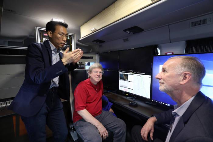 ETRI 연구진이 시연차량 내부에서 방송망과 통신망 연동 기술에 대해 설명하는 모습
