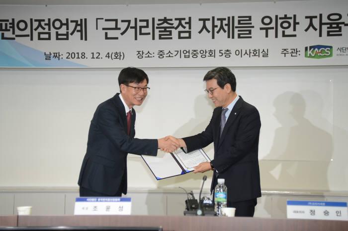 김상조 공정거래위원장(왼쪽)이 조윤성 한국편의점산업협회장으로부터 편의점 자율규약 이행 확인서를 전달받고 악수하고 있다.