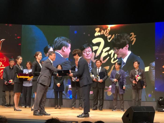 김호락 스튜디오버튼 총감독(오른쪽)이 2018 대한민국 콘텐츠대상 시상식에서 도종환 문화체육관광부장관으로부터 수상하고 있다.