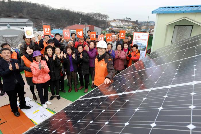 한화그룹 관계자와 지역 주민이 해피선샤인 캠페인으로 설치한 태양광 발전설비 앞에서 기념촬영했다. [자료:한화그룹]